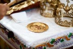 Guldbröllopcirklar nära altaret i kyrkan för bröllopparen av den traditionella religiösa bröllopceremonin royaltyfri bild