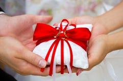 Guldbröllopcirklar på den röda och vita cirkelkudden i händer av bruden och brudgummen Arkivbilder