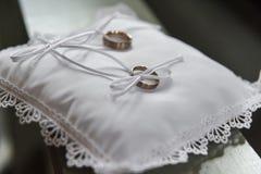 Guldbröllopcirklar på satängkudden i kyrka royaltyfria bilder