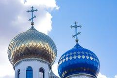 Guldpläterad och blå kupol av en kyrka med kors, mot en bakgrund för blå himmel royaltyfri foto