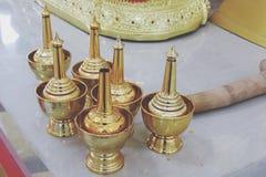 Guldpläterade metallvattenkoppar, vatten-baserade objekt i buddistiska ceremonier i tempel arkivfoton