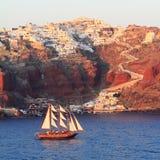 Gulet που πλέει μπροστά από Oia και Athinios το λιμάνι  Στοκ Φωτογραφία