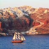 Gulet Sailing In Front Of Oia And Athinios Harbor. View of Oia west and Anthinios harbor from the sea in a summer day, at sunset, with a gulet sailing Stock Photography