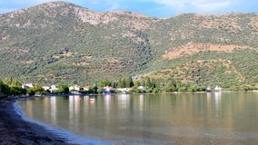 Gulf of Corinth Bay, Late Afternoon, Greece. View across a Gulf of Corinth Bay, Ormos Lemonias, to fishing and holiday village buildings and olive tree covered royalty free stock image