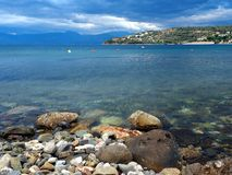 Gulf of Corinth Fishing Village, Greece. Gulf of Corinth bay, clean waters and rocky shore, with early morning storm cloud light, Greece Stock Photography