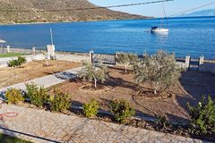 Gulf of Corinth House and Bay, Greece. View of a modern yacht moored in a Gulf of Corinth bay over the garden with roses and olive trees of a bay side house Royalty Free Stock Photo