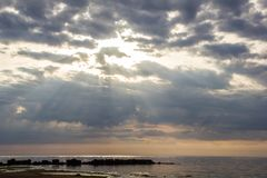 The Gulf of Finland before sunset, the rays of the sun pass through the overcast sky royalty free stock photo