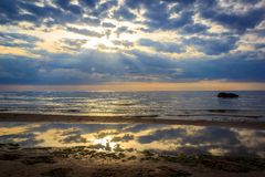 The Gulf of Finland before sunset, the rays of the sun pass through the overcast sky royalty free stock images