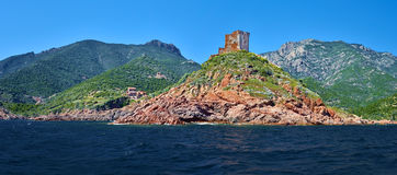 Gulf of Girolata coastline dominated by Genoese Tower. The landscape seen from sea when approaching Girolata Anchorage, Corsica Island, Corse-du-Sud, France Stock Image