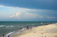 Gulf of Thailand beach beside Hatyai Pattani highway southern Thailand. Pattani, Thailand - May 6, 2017: Kids and families wade and swim at a Gulf of Thailand Royalty Free Stock Image