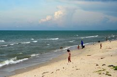 Gulf of Thailand beach beside Hatyai Pattani highway southern Thailand. Pattani, Thailand - May 6, 2017: Kids and families wade and swim at a Gulf of Thailand Royalty Free Stock Photo