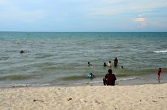 Gulf of Thailand beach beside Hatyai Pattani highway southern Thailand. Pattani, Thailand - May 6, 2017: Kids and families wade and swim at a Gulf of Thailand Stock Photography