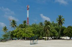 "GULHI海岛,马尔代夫†""2017年11月:在棕榈树背景的橄榄球场和电信耸立 免版税库存照片"