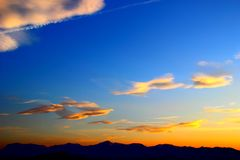 Guling-blått solnedgånghimmel med moln över konturerna av bergen arkivfoto