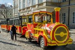 Guling och den röda turnera bilen i form av ett drev med vagnar som väntar på turister som landar på en turnera, är en solig dag  Royaltyfri Fotografi