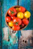 Guling och röda körsbärsröda tomater i en bunke på den lantliga trätabellen Arkivbilder