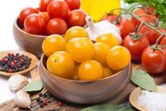 Guling och röda körsbärsröda tomater i träbunkar Royaltyfri Foto