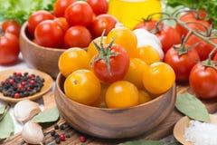 Guling och röda körsbärsröda tomater i träbunkar som är horisontal Arkivbild