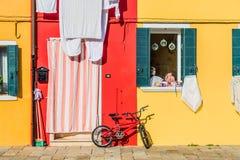 Guling och rött hus med en cykel Färgrika hus i den Burano ön nära Venedig, Italien Venedig vykort Berömt ställe för Europa Royaltyfria Foton