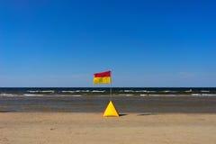 Guling-röd flagga på stranden av Östersjön i sommaren Fotografering för Bildbyråer