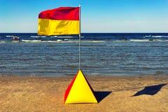 Guling-röd flagga på stranden av Östersjön i sommaren Arkivbilder