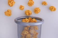Guling skrynklade pappers- bollar som rullar ut ur en soptunna Royaltyfri Fotografi