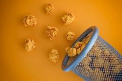 Guling skrynklade pappers- bollar som rullar ut ur en soptunna Royaltyfri Foto