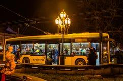 Guling står på spårvagnelektroniken som stoppar och väntar på stiga ombord natten på fyrkanten i Lviv Royaltyfri Foto