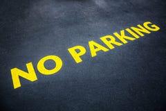 Guling uttrycker ingen parkering som målas på vägasfalten Royaltyfri Foto