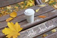 Gulingsidor och kopp av cofee på bänken med den titelHello hösten Arkivfoto