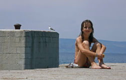 Gull and girl in vacation. Gull and smiling girl in vacation on sea port near the Adriatic sea Royalty Free Stock Photography