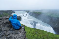 Tourist looks at the big waterfall in Iceland Royalty Free Stock Image
