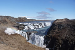 Gullfoss rainbow in icy waterfall. The icy Gullfoss waterfall and rainbow in the Hvita (white) river in spring in Iceland Stock Image