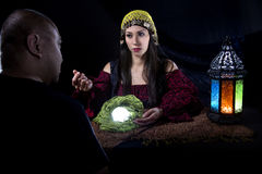 Gullible Fraud Victim. Gullible patron with scam artist or fraudulent psychic fortune teller stock photo