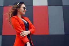 Gullig älskvärd ung kvinna i solglasögon, rött omslag, modehatt som står över utomhus- abstrakt bakgrund stående för modemodell Arkivfoto