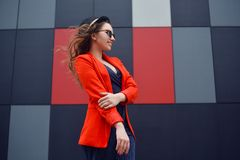Gullig älskvärd ung kvinna i solglasögon, rött omslag, modehatt som står över utomhus- abstrakt bakgrund stående för modemodell Royaltyfri Fotografi