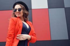 Gullig älskvärd ung kvinna i solglasögon, rött omslag, modehatt som står över utomhus- abstrakt bakgrund stående för modemodell Royaltyfria Foton
