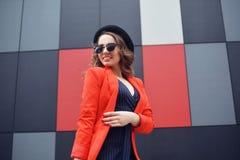Gullig älskvärd ung kvinna i solglasögon, rött omslag, modehatt som står över utomhus- abstrakt bakgrund stående för modemodell Royaltyfria Bilder