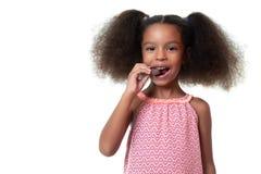 Gullig afrikansk amerikanflicka som äter en chokladkaka royaltyfri foto