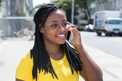Gullig afrikansk amerikankvinna i en gul skjorta på mobiltelefonen Arkivfoton