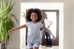 Gullig afrikansk unge som kör i nytt hus på rörande dag arkivfoton
