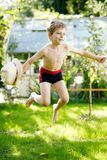 Gullig aktiv ungepojkebanhoppning i trädgården på varm solig sommardag Lycklig unge som ser kameran Förtjusande barn med arkivfoton