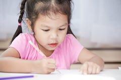 Gullig asiatisk barnflicka som har gyckel som drar och som ska målas med färgpennan Royaltyfri Fotografi