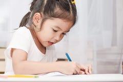 Gullig asiatisk barnflicka som har gyckel som drar och som ska målas med färgpennan Royaltyfria Foton