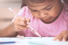 Gullig asiatisk barnflicka som har gyckel som drar och som ska målas Royaltyfri Fotografi