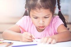Gullig asiatisk barnflicka som har gyckel som drar och som ska målas Royaltyfria Bilder