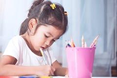 Gullig asiatisk barnflicka som har gyckel som drar och som ska målas med färgpennan Royaltyfria Bilder