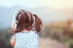 Gullig asiatisk barnflicka som har gyckel som lyssnar musiken royaltyfri bild