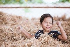 Gullig asiatisk barnflicka som har gyckel som spelar med höbunten arkivfoton