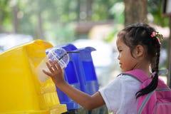 Gullig asiatisk barnflicka som kastar plast- exponeringsglas i återvinningavfall royaltyfria bilder